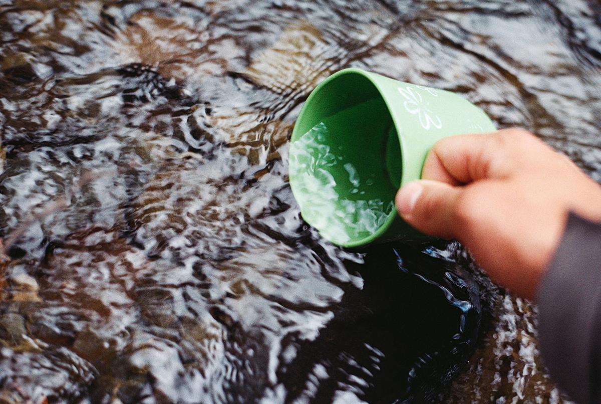 Tazza smaltata e fonte di acqua minerale