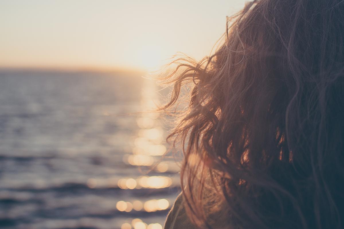 Donna con capelli ricci davanti al sole e al mare