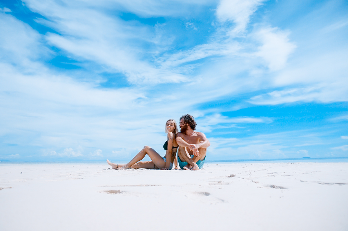 Coppia su spiaggia di sabbia bianca